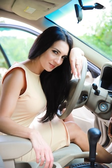Happy, beautiful young girl with dark hair in a car salon on the street