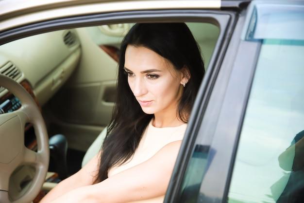 通りの車のサロンで黒髪の幸せで美しい少女