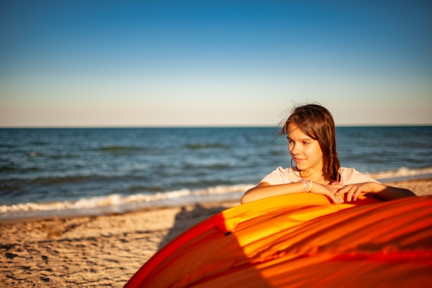 Happy beautiful young girl with dark hair stands near a bright tent smiling on the sandy beach of the blue shining sea