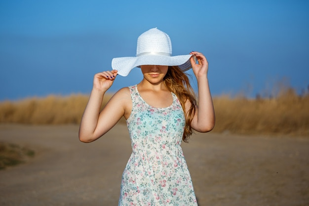 Happy beautiful young girl with hat on natural background on sunny day.
