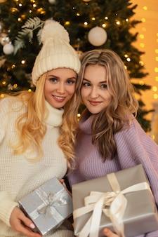 ヴィンテージのセーターと帽子とファッショナブルなニットの服を着た幸せな美しい若い女の子は、クリスマスツリーとライトの背景にクリスマスプレゼントを保持しています。冬休み