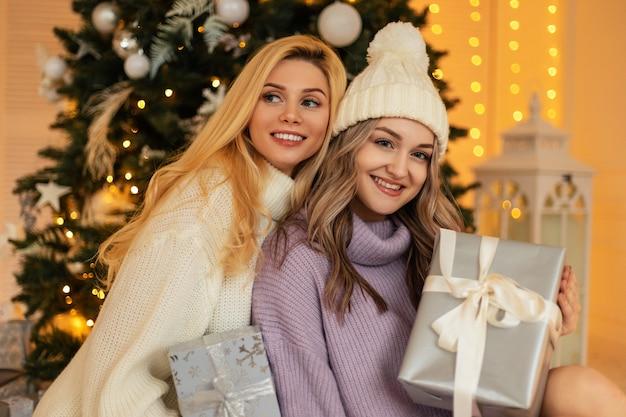 クリスマスツリーの近くに、ファッショナブルなニットのセーターとギフト付きのヴィンテージのウールの帽子をかぶった笑顔の幸せな美しい若い女の子が座っています。冬休み