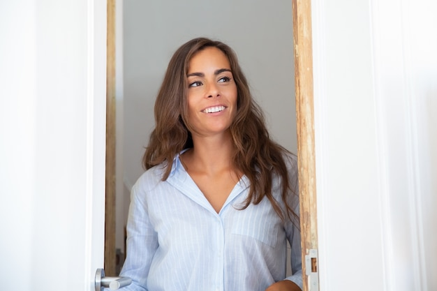 Happy beautiful young hispanic woman opening door, standing in doorway, looking inside apartment and smiling