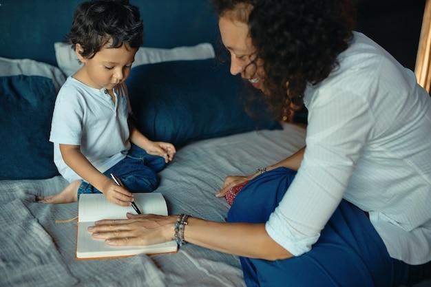 Felice bella giovane donna latina seduta sul letto con il suo piccolo figlio carino, mettendo la mano sulla carta e tracciando i suoi contorni usando la matita.