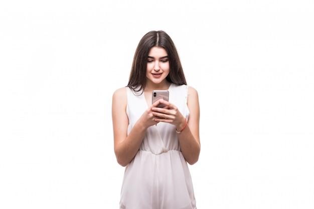 Felice bella giovane modella in abito bianco moderno su bianco con il telefono