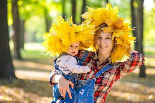 Счастливая красивая молодая мать с ребенком на руках в парке осенью.