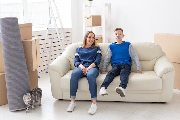 행복 한 아름 다운 젊은 미혼모와 긍정적 인 아들은 옆에 소파에 앉아있다