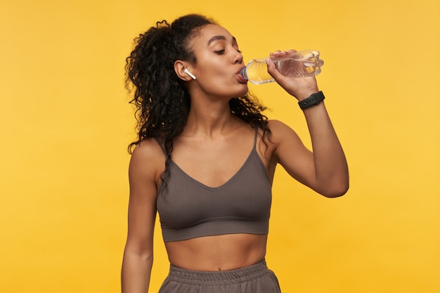 Felice bella giovane sportiva che ascolta la musica usando gli auricolari wireless e bevendo acqua dalla bottiglia isolata sul muro giallo