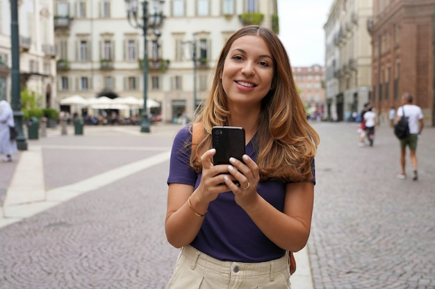 カメラを見て、ぼやけた街の背景と屋外で携帯電話を保持している幸せな美しい若い学生の女の子。シティライフスタイルピープルテクノロジー。