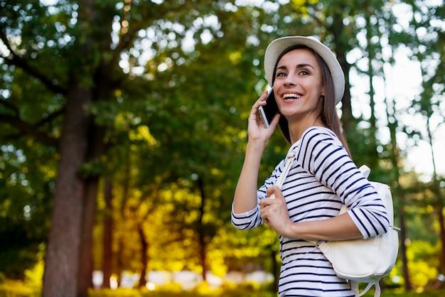 彼女は公園で屋外を歩いている間、スマートフォンとバックパックで帽子をかぶった幸せな美しい若い学生女性