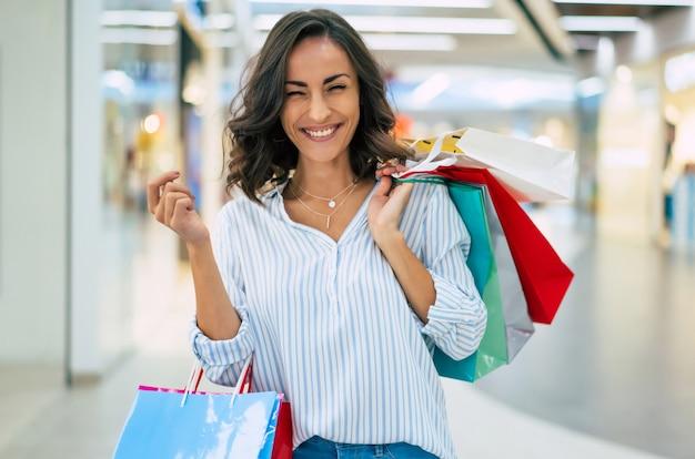 Счастливая красивая молодая стильная женщина с хозяйственными сумками, идущая в торговом центре