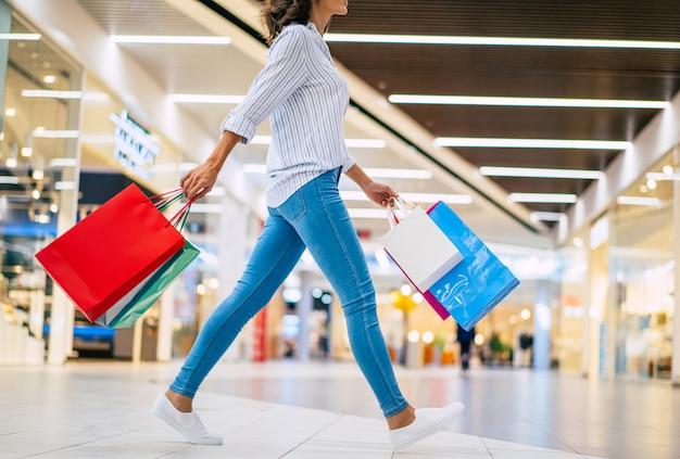 쇼핑몰에서 산책하는 쇼핑 가방과 함께 행복 한 아름 다운 젊은 세련 된 여자