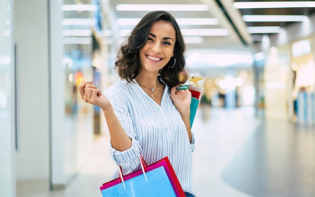 Happy beautiful young stylish woman with shopping bags walking in the mall