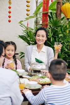 Happy beautiful young vietnamese woman enjoying lunar new year celebration with her family, decorations with best wishes inscription in background