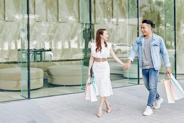 다른 상점에 걸을 때 남자 친구의 손을 당기는 행복 한 아름 다운 젊은 베트남 여자