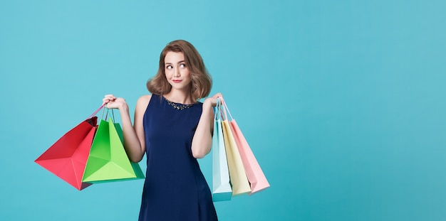Happy beautiful young woman in blue dress and hand holding shopping bags and looking at on light blue with copy space.