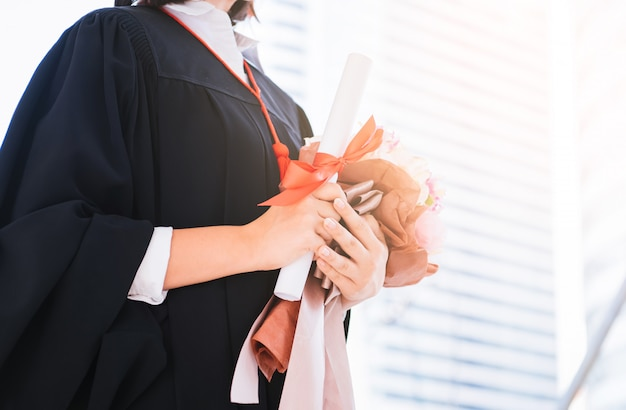 Happy beautiful young woman graduate hand holding diploma and flower bouquet at graduate ceremony.