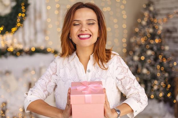 Счастливая красивая молодая женщина, держащая подарочную коробку
