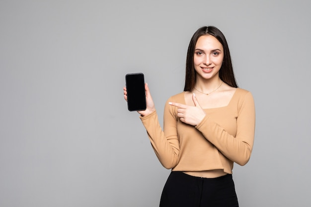 Happy beautiful young woman holding blank screen mobile phone over grey wall