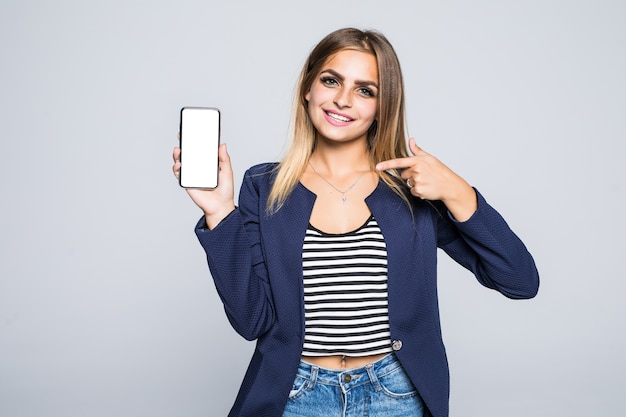 Happy beautiful young woman holding blank screen mobile phone and pointing finger over white wall