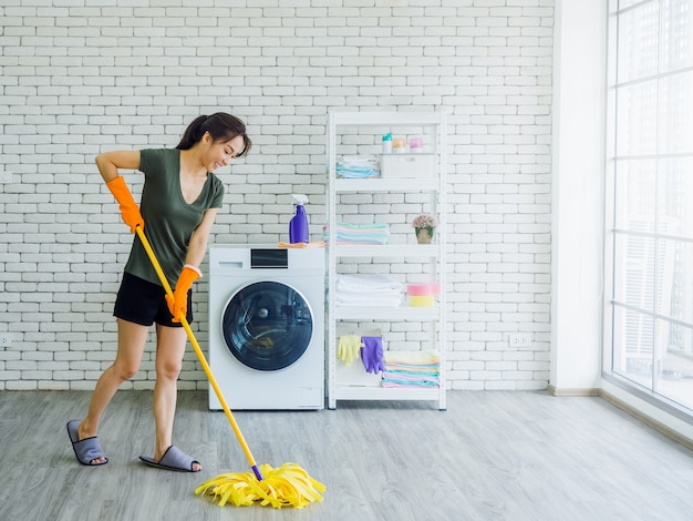 Happy beautiful young woman, housewife wearing orange protective rubber gloves with smiling face cleaning floor with mop near wash machine on white brick wall near huge glass window.