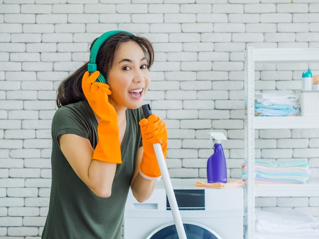 Happy beautiful young woman, housewife wearing orange rubber gloves, listening music with green headphone singing fun with mop like a microphone on white brick wall in home.