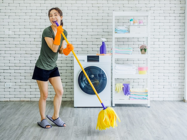 Happy beautiful young woman, housewife wearing orange rubber gloves and slipper singing fun with yellow mop while cleaning floor near wash machine on white brick wall.