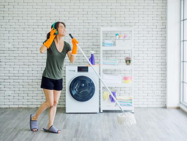 Счастливая красивая молодая женщина, домохозяйка в резиновых перчатках, тапочках и зеленых наушниках поет весело со шваброй, как микрофон, убирая пол возле стиральной машины на белой стене.