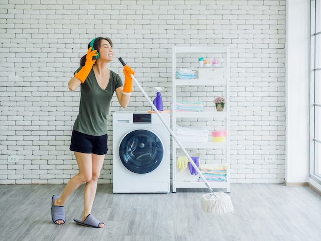 Happy beautiful young woman, housewife wearing rubber gloves, slipper and green headphone singing fun with mop like a microphone while cleaning floor near wash machine on white wall.