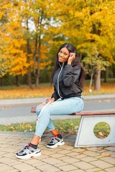 Счастливая красивая молодая женщина в модной одежде с джинсами и кроссовками сидит на скамейке в осеннем парке