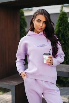 通りに立って、コーヒーを保持しているスポーツウェアの幸せな美しい若い女性。女性のファッション。都市のライフスタイル