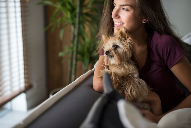 彼女の犬と一緒に窓を見て幸せな美しい若い女性