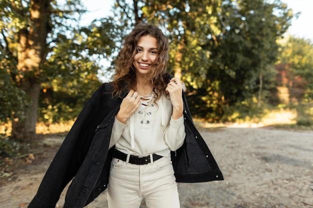 곱슬머리에 데님 재킷과 스웨터를 입은 세련된 청바지 옷에 웃는 얼굴을 한 행복한 아름다운 젊은 여성 모델은 공원의 나무 근처에서 자연을 산책합니다.