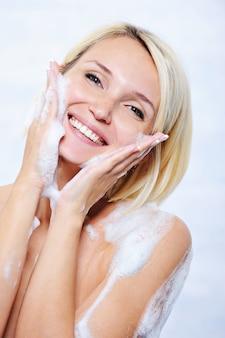 Bella giovane donna felice che si distende nella stanza da bagno