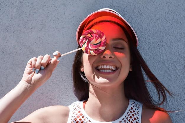 Счастливая красивая молодая женщина катается на роликах, ест леденцы летние фото