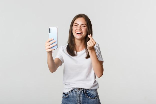 Счастливый красивая молодая женщина, показывая жест сердца и принимая selfie на смартфоне, беззаботно смеясь.