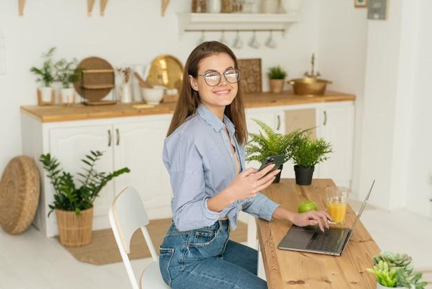 Счастливая красивая молодая женщина, сидя за столом у себя дома, проходит курсы в интернете и ведет прямую трансляцию. работа и учеба из дома в условиях карантина.