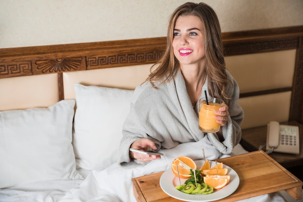 Happy beautiful young woman sitting on bed holding glass of juice and mobile phone looking away