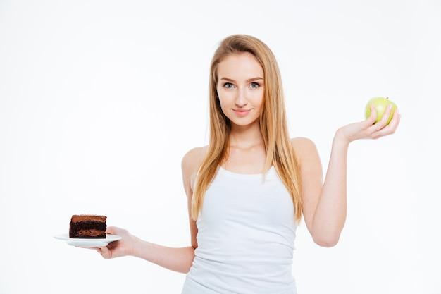 Счастливая красивая молодая женщина, стоящая и держащая шоколадный торт и зеленое яблоко на белом фоне