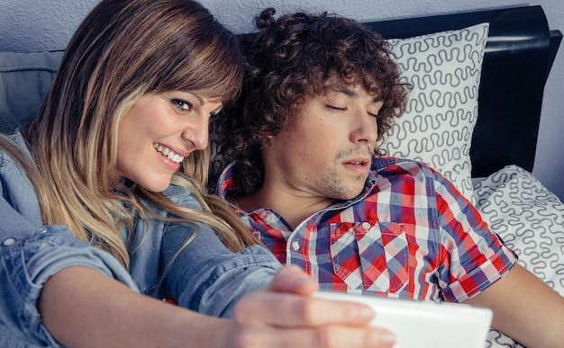ベッドの上で寝ている男性にスマートフォンで写真を撮る幸せな美しい若い女性。自宅での余暇のコンセプト。