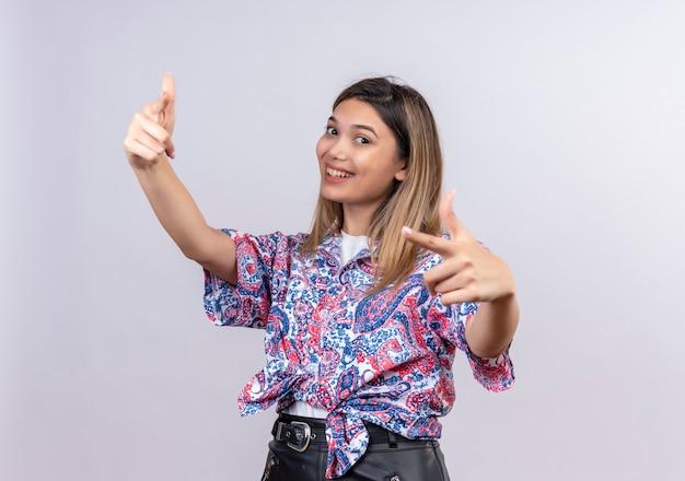 Una bella giovane donna felice che indossa la camicia stampata paisley che punta con il dito indice mentre guarda su un muro bianco