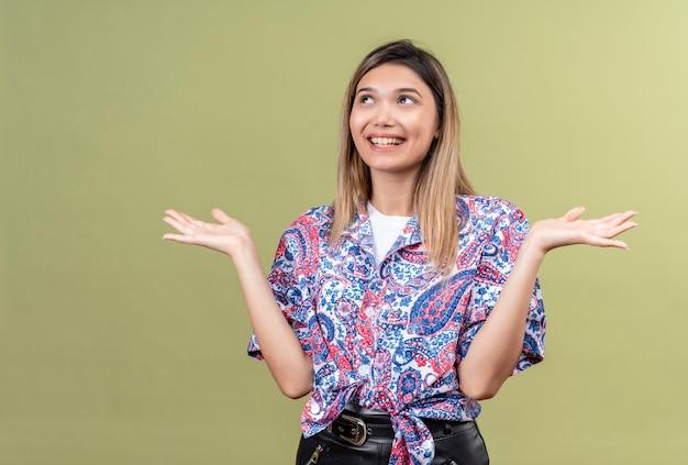 Una bella giovane donna felice che indossa la camicia stampata paisley che sorride e che apre le mani mentre osserva in su su una parete verde