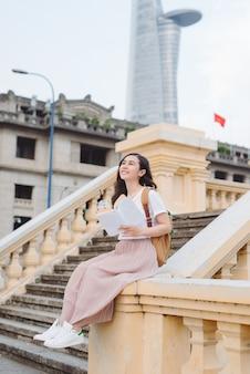 バックパックと屋外の階段に座っている本と幸せな美しい若い女性