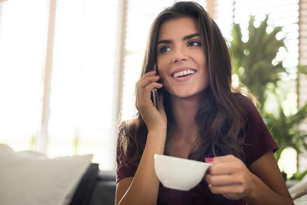 커피 컵과 전화로 이야기와 함께 행복 한 아름 다운 젊은 여자