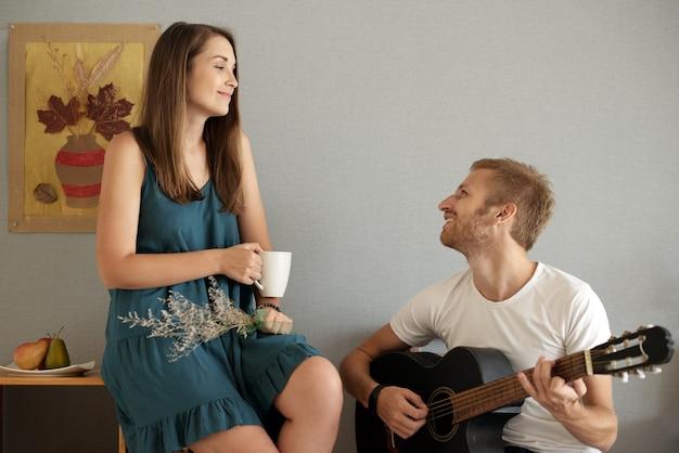 웃는 남자친구가 기타를 연주하고 서명하는 모습을 바라보며 커피 한 잔을 들고 행복한 아름다운 젊은 여성