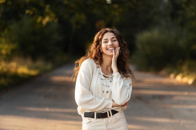 곱슬 머리와 니트 스웨터에 이빨을 가진 아름다운 미소를 가진 행복한 아름다운 젊은 여성이 자연의 공원에서 산책합니다. 여성 예쁜 웃는 얼굴