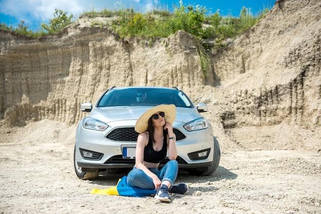 夏の道で彼女の車の近くに立っているウクライナの旗を持つ幸せな美しい若い女性