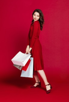Happy beautiful young woman with his hand holding shopping bags