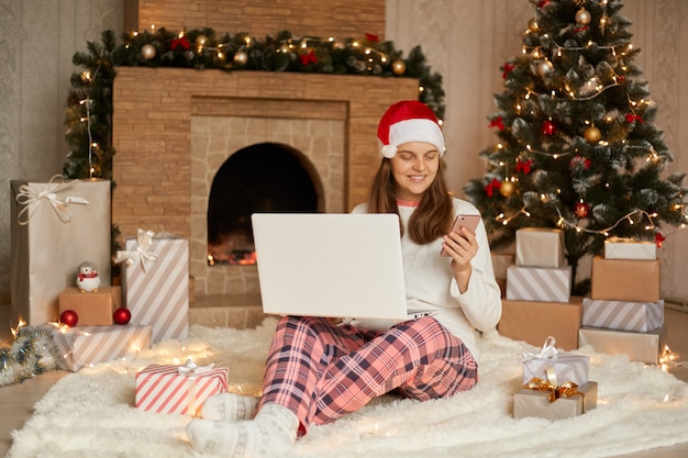 Happy beautiful young woman with laptop on knees sitting near christmas tree and fireplace on floor, holding phone in hands, sending message with congratulating, looks glad.