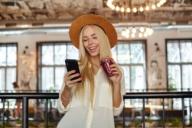 Felice bella giovane donna con il telefono in mano guardando lo schermo e sorridendo amorevolmente, bere frullato con paglia, indossa una camicia bianca e cappello marrone